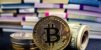 Монета биткоин и свернутые купюры