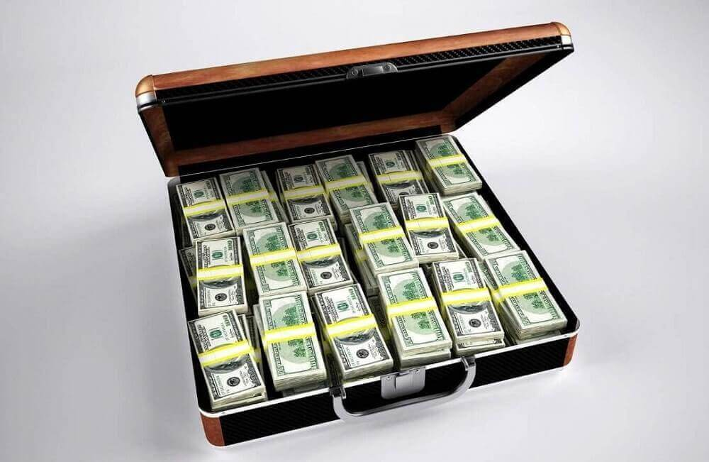 Чемодан денег на сером фоне