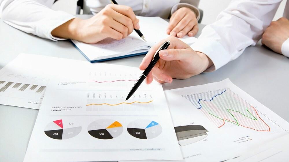Mужская рука указывает на график, женская пишет план